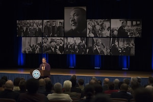 A retired soldier stands in front of eight images of Dr. Martin Luther King Jr.