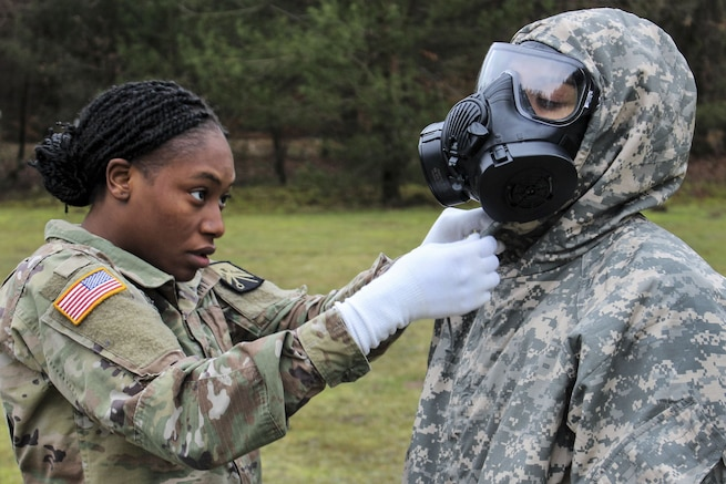 A soldier helps another soldier remove a chemical protective suit.