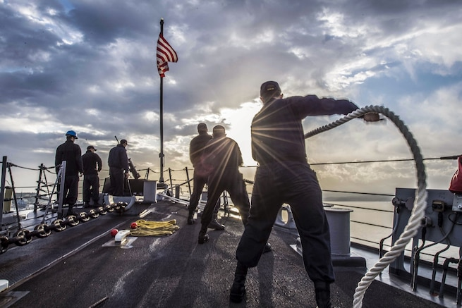 Sailors, shown from behind, maneuver mooring lines on a ship, with sunbeams, clouds and sea in the background.