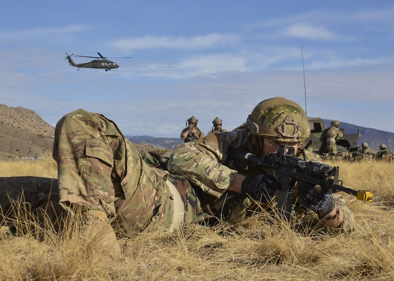 A student from the U.S. Air Force Pararescue School shields a wounded Airman while engaging in small arms fire during a mass casualty exercise Jan. 6, 2018 at Kirtland Air Force Base, N.M. The exercise, part of a sequence of full mission profiles pararescuemen and combat rescue officer students must face before graduation, included more than 100 Airmen and Soldiers. Members of the 3-501st Air Assault Brigade from Fort Bliss, Texas, provided the air component with UH-60 Blackhawk helicopters. (U.S. Air Force photo by Jim Fisher)