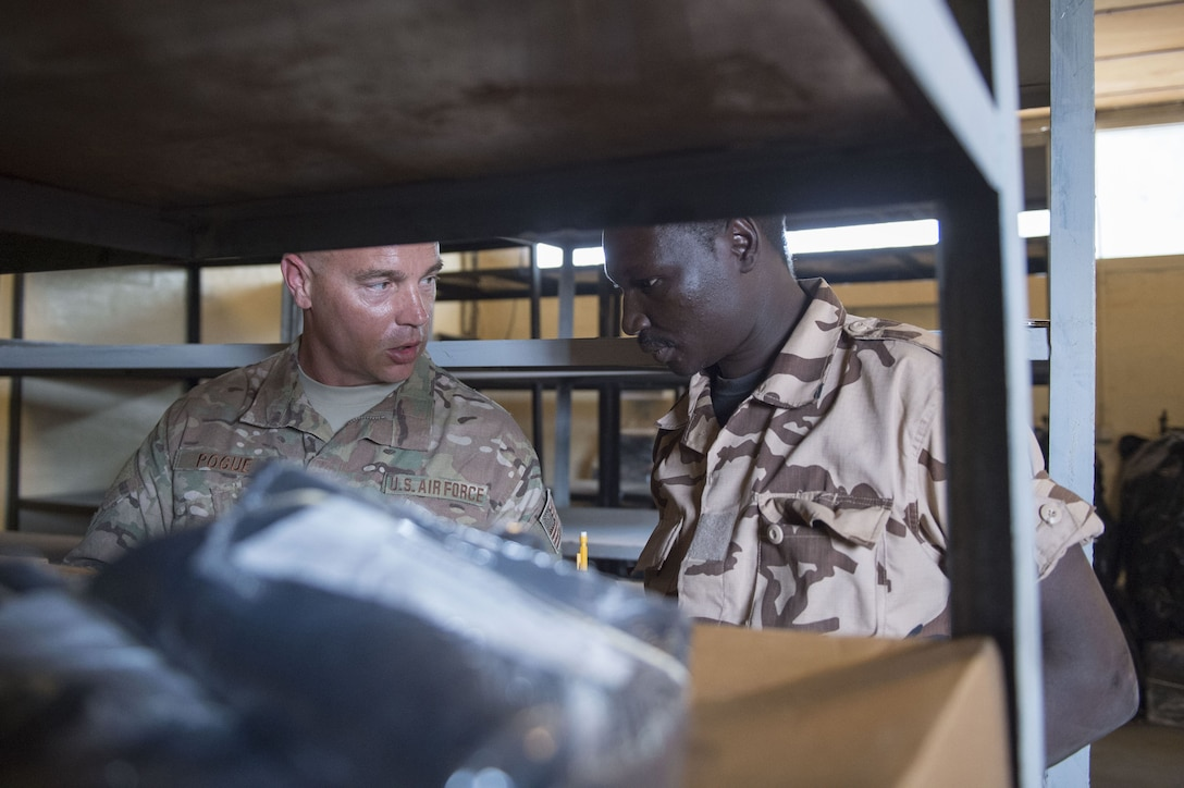 Master Sgt. Jonathan Pogue, 818th Mobility Support Advisory Squadron air advisor, walks through inventory procedures with a Chadian Air Force Airman during a mobile training team event at Adjikossei Air Base, N'Djamena, Chad, January 15, 2018.