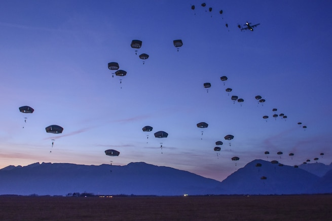 Dozens of parachutes descend against a backdrop of deep blue sky and dark blue mountains.