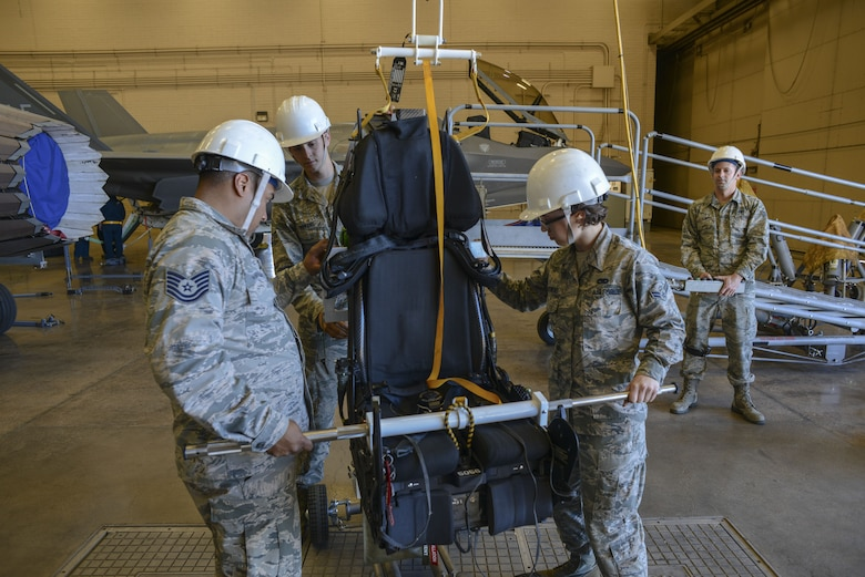 Airmen assigned to the 56th Component Maintenance Squadron guide an F-35A Lightning II ejection seat onto a cart for maintenance at Luke Air Force Base, Ariz., Jan. 11, 2018. In May 2017, three modifications were implemented to the F-35 ejection system to remove the 136 pound weight limit restriction. (U.S. Air Force photo/Airman 1st Class Caleb Worpel)
