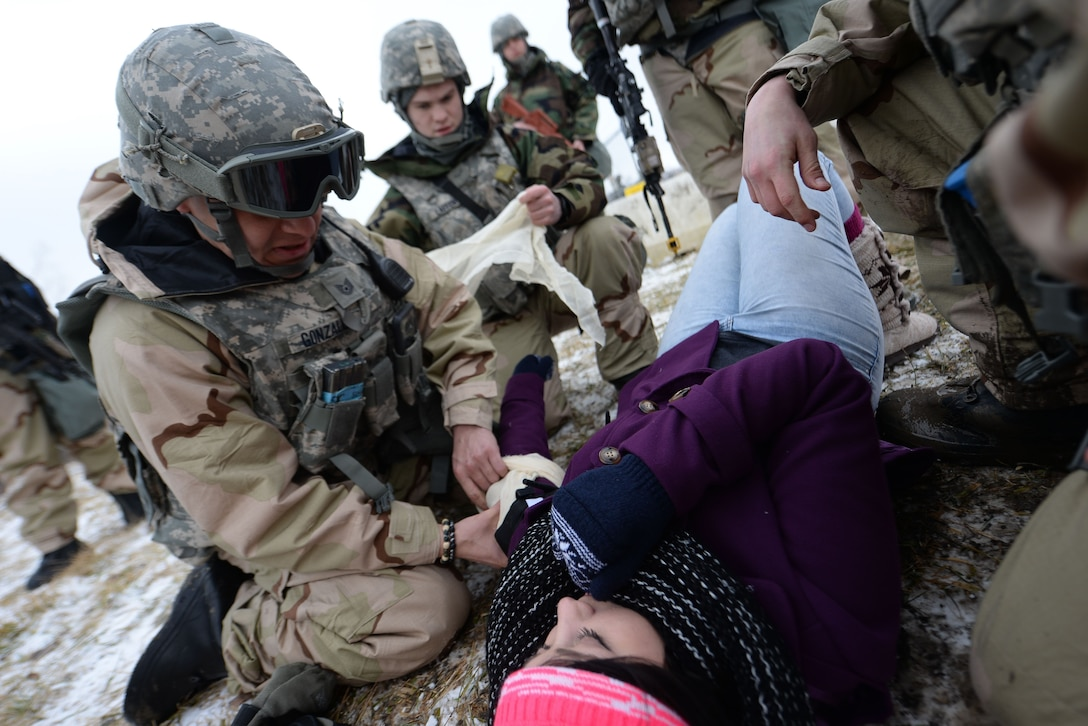 Members of the 55th Security Forces Squadron perform self aid buddy care on an individual during an operational readiness exercise at Offutt Air Force Base, Nebraska, Jan. 23, 2018. The exercise tested the 55th Wing's readiness and ability to meet wartime and contingency taskings.