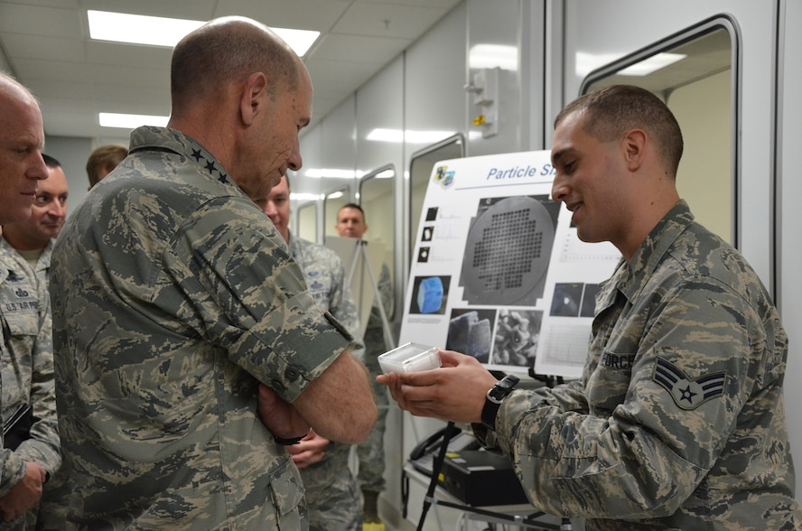 Senior Airman Dylan B. Melone (right), a clean room technician with the Air Force Technical Applications Center, shows Gen. Mike Holmes, commander of Air Combat Command, a transmission electron microscope grid he uses to accomplish AFTAC's trace particle analysis mission.  Holmes visited the nuclear treaty monitoring center, Patrick AFB, Fla., Jan. 24, 2018.  (U.S. Air Force photo by Susan A. Romano)