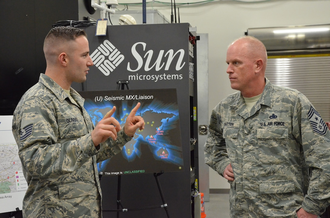 Tech. Sgt. Peter J. Oliveri (left), noncommissioned officer in charge of seismic field maintenance for the Air Force Technical Applications Center, Patrick AFB, Fla., discusses seismic operations with Chief Master Sgt. Frank Batten, command chief of Air Combat Command, during the chief's visit to the nuclear treaty monitoring center Jan. 24, 2018. Oliveri was one of many AFTAC Airmen who briefed Batten on the center's global mission.  (U.S. Air Force photo by Susan A. Romano)