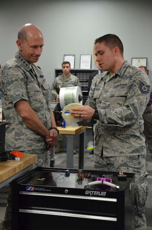 Tech. Sgt. Donald E. Kramer II, noncommissioned officer in charge of Innovation Operations for the Air Force Technical Applications Center, shows Gen. Mike Holmes, commander of Air Combat Command, a prototype of an early iteration of a materials program carousel created by AFTAC's Innovation Lab.  This was Holmes' first visit to the Department of Defense's sole nuclear treaty monitoring center at Patrick AFB, Fla.  (U.S. Air Force photo by Susan A. Romano)