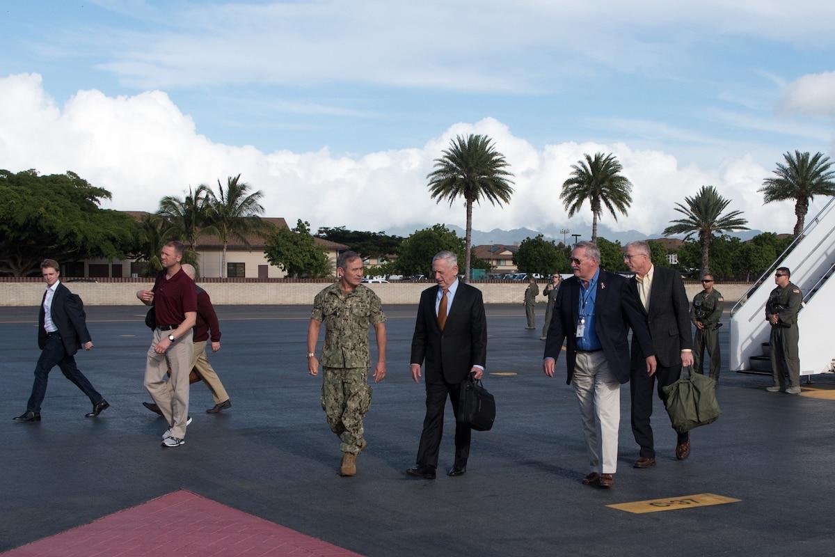 Defense Secretary James N. Mattis is greeted on a runway.