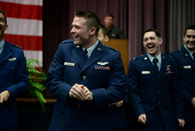 Second Lt. Denis Aurelious, 14th Student Squadron student pilot, attempts to break his first set of wings during Specialized Undergraduate Pilot Training Class 18-04's graduation Jan, 19, 2018, on Columbus Air Force Base, Mississippi. At the end of every graduation the pilots break their first set of wings as tradition promoting good luck throughout their flying career. (U.S. Air Force photo by Airman 1st Class Keith Holcomb)