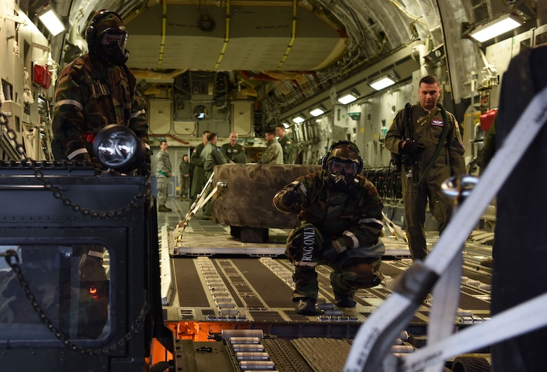 Airmen assigned to 62nd Airlift Wing and 627th Air Base Group load a C-17 Globemaster III during Exercise Winterhook at Joint Base Lewis-McChord, Wash., Jan. 25, 2018. During the exercise, Team McChord Airmen were tested and evaluated on their ability to properly wear mission oriented protective posture gear, perform their day-to-day duties and administer self-aid and buddy care during a simulated chemical threat. (U.S. Air Force photo by Senior Airman Tryphena Mayhugh)