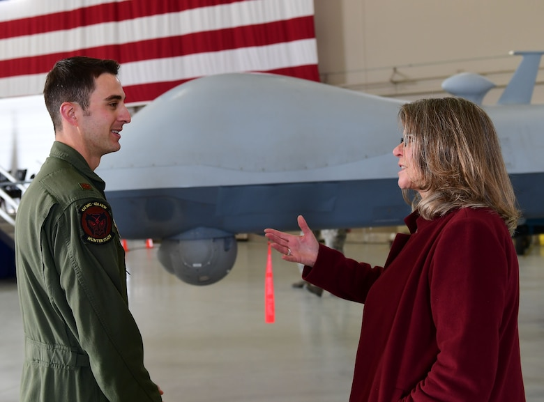 "Ms. Jonna Doolittle Hoppes, executive director of the Doolittle Foundation and granddaughter of Gen. James ""Jimmy"" Doolittle, speaks to Maj. Matthew, 432nd Wing pilot, Jan. 18, 2018, at Creech Air Force Base, Nev. Ms. Doolittle Hoppes toured the base with retired Lt. Gen. Christopher Miller, president of the Air Force Historical Foundation, before presenting the General James H. ""Jimmy"" Doolittle award to the 432nd Wing/432nd Air Expeditionary Wing. (U.S. Air Force photo/Senior Airman Christian Clausen)"