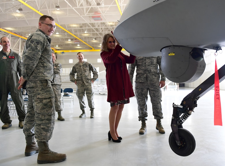 "Ms. Jonna Doolittle Hoppes, executive director of the Doolittle Foundation and granddaughter of Gen. James ""Jimmy"" Doolittle, lifts the nose of an MQ-1 Predator off the ground Jan. 18, 2018, at Creech Air Force Base, Nev. Ms. Doolittle Hoppes toured the base with retired Lt. Gen. Christopher Miller, president of the Air Force Historical Foundation, before presenting the General James H. ""Jimmy"" Doolittle award to the 432nd Wing/432nd Air Expeditionary Wing. (U.S. Air Force photo/Senior Airman Christian Clausen)"