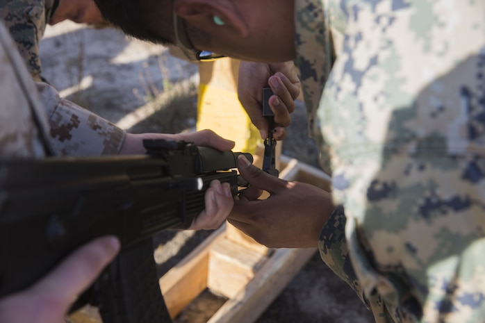 A tactics instructor with the I Marine Expeditionary Force Advisor Training Branch adjusts the sights on an AK-47 assault rifle as part of a foreign weapons demonstration for Marines with Task Force Al-Taqaddum 18.