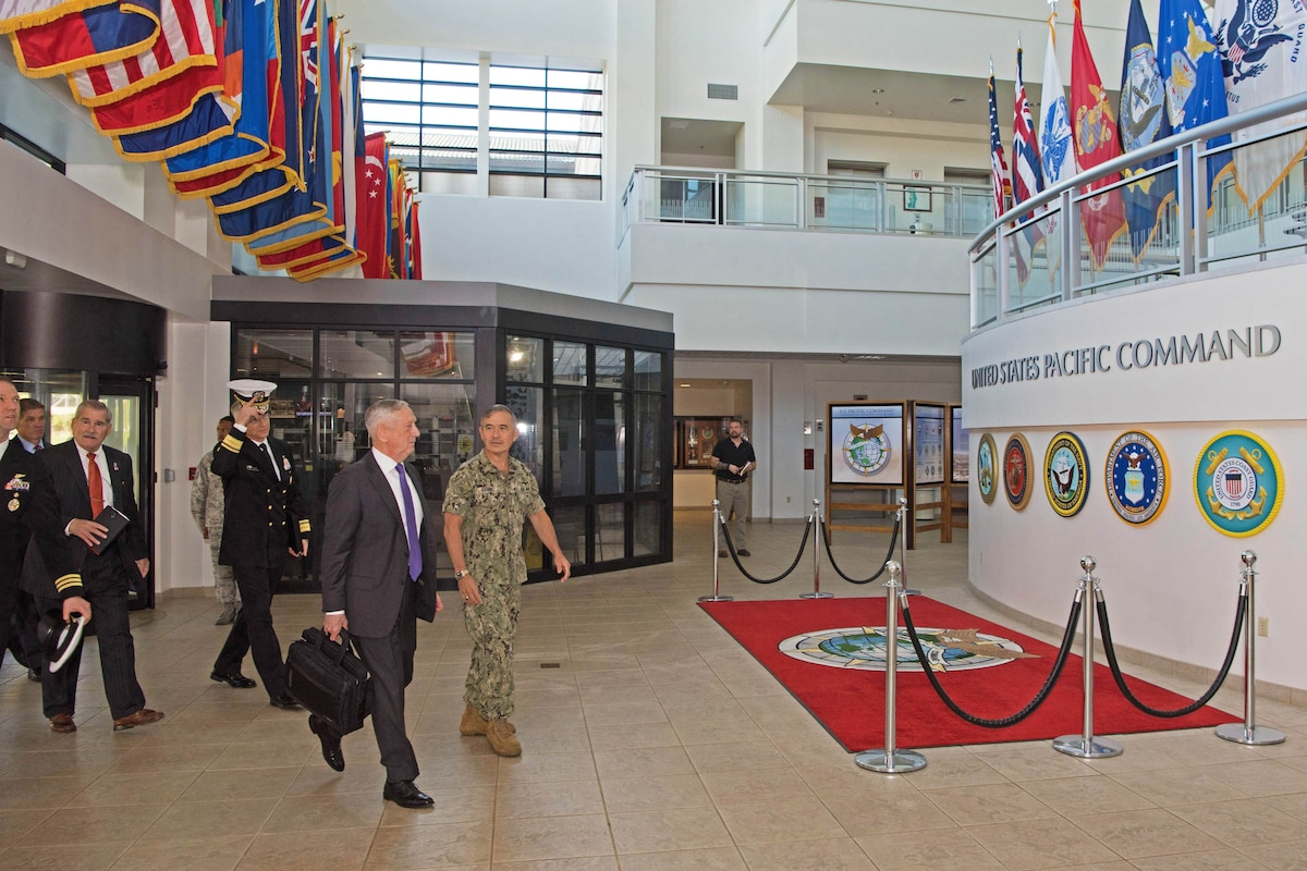 Defense Secretary James N. Mattis walks with the U.S. Pacific Command commander in a building lobby.