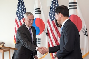 Defense Secretary James N. Mattis shake hands with his South Korean counterpart in front of a wall of flags.
