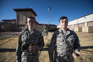 Air Force Airmen 1st Class Jason Brock and Kolton McCasland, 27th Special Operations Support Squadron weather apprentices, pose for a portrait in front of a weather sensor at Cannon Air Force Base, N.M., Jan. 24, 2018. Weather forecasters use several sensors across base to accurately measure weather patterns in the area. Air Force photo by Senior Airman Lane T. Plummer