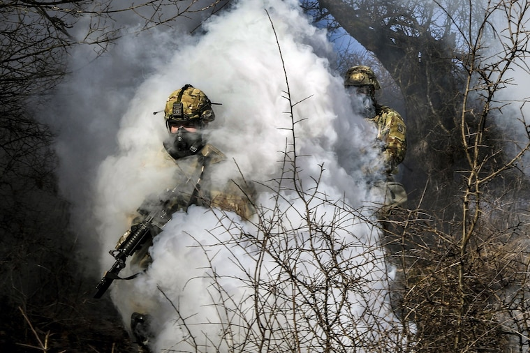 Two soldiers wearing protective masks move through a thick white smoke cloud.