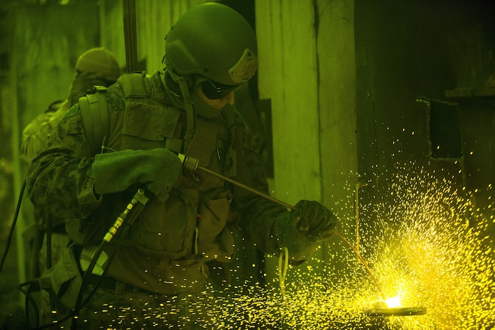 A Marine from Methods of Entry School on Marine Corps Base Quantico uses a torch to cut a through a ship door. This photo was taken with shade 5 safety goggles over the camera lens. Marines assigned to MOES come from different MOS's such as Reconnaissance and Force Reconnaissance units, Security Forces Regiment Recapture Tactics teams, Military Police Special Reaction teams, Explosive Ordnance Disposal units and Marine Special Operations Command units.