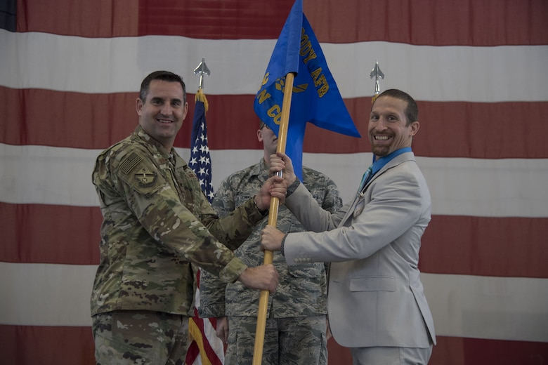 Col. Jeffrey Valenzia, 93d Air Ground Operations Wing commander, hands the guidon to Kelly Barcol, incoming 93d AGOW honorary commander, during an Honorary Commander Change of Command ceremony at Moody Air Force Base, Ga., Jan. 26, 2018. The Honorary Commander Program allows local community leaders to gain awareness of Moody's mission through official and social functions. (U.S. Air Force Photo by Staff Sgt. Olivia Dominique)