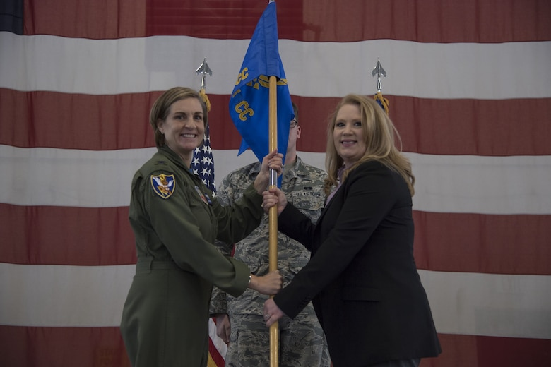Col. Jennifer Short, 23d Wing commander, hands Paige Dukes, incoming 23d WG honorary commander, the guidon during an Honorary Commander Change of Command ceremony at Moody Air Force Base, Ga., Jan. 26, 2018. The Honorary Commander Program allows local community leaders to gain awareness of Moody's mission through official and social functions. (U.S. Air Force photo by Staff Sgt. Olivia Dominique)
