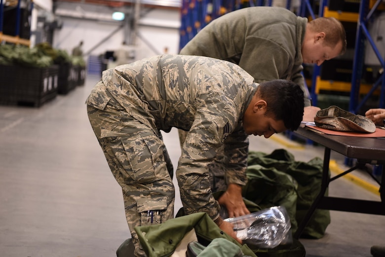 U.S. Airmen assigned to the 86th Logistics Readiness Group check duffel bags to ensure all of their individual protection equipment is accounted for on Ramstein Air Base, Germany Jan. 26, 2018. The 86th LRG began their mobility exercise in early morning at 5 a.m. and ended at 5 p.m.