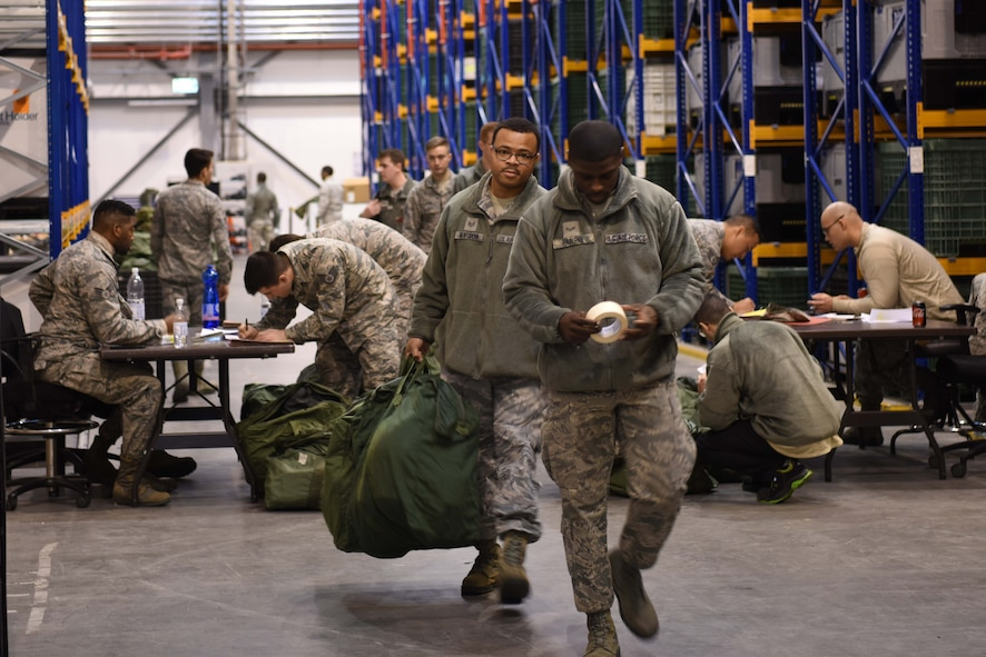 U.S. Air Force Staff Sgt. Hammeed Seifuddin 86th Munitions Squadron, stockpile management crew chief, follows an escort out of the building after receiving his mobility equipment on Ramstein Air Base, Germany Jan. 26, 2018. The 86th LRG conducted a mobility exercise in their building.