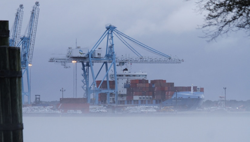 Fog settles in along the Elizabeth River as cranes offload cargo from a ship docked at the Portsmouth Marine Terminal in Portsmouth, Virginia.
