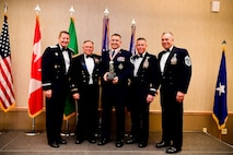 Master Sgt. Jeremy Montgomery, a recruiter with the Washington Air National Guard, is presented with the Recruiting and Retention Manager of the Year trophy at the Washington Air National Guard's 9th Annual Awards Banquet held at the American Lake Conference Center on Joint Base Lewis-McChord, Washington, Jan. 27, 2018.  Montgomery was awarded the trophy for his outstanding contributions to the Washington Air National Guard over the last year.  Pictured from left to right are: Gen. Robin Rand, Air Force Global Strike Command and Air Forces Strategic-Air, U.S. Strategic Command commander; Maj. Gen. Bret Daugherty, Adjutant General of the Washington National Guard, Montgomery, Montgomery, Brig. Gen. Jeremy Horn, commander of the Washington Air National Guard, and Chief Master Sgt. Max Tidwell, Washington Air National Guard command chief. (U.S. Air National Guard photo by Tech. Sgt. Timothy Chacon)