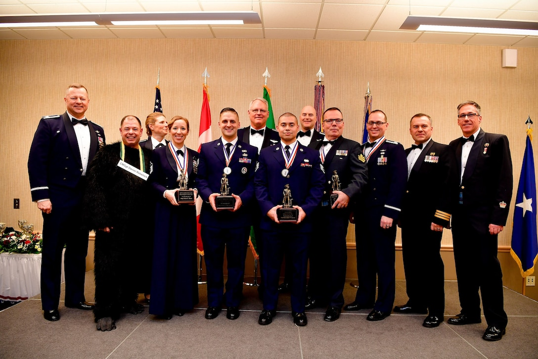 Annual award winners from the Western Air Defense Sector pose for a picture during the Washington Air National Guard's 9th Annual Awards Banquet held at the American Lake Conference Center on Joint Base Lewis-McChord, Washington, Jan. 27, 2018.  Pictured from left are: Col. Gregor Leist, WADS commander, Chief Master Sgt. Daniel Rebstock, WADS senior enlisted advisor, Col. Paige Abbott, 225th Support Squadron commander, Master Sgt. Dawn Kloos, 225th Air Defense Group first sergeant, Staff Sgt. Aaron DeCremer, 225th Air Defense Squadron, Col. William Krueger, 225th Air Defense Group commander, Staff Sgt. Christopher LaCour, 225th SS, Col. Brett Bosselmann, 225th ADS commander, Royal Canadian Air Force Sgt. Yves Truchon, 225th ADS and Canadian Detachment, Capt. Joseph Hale, 225th SS, RCAF Lt. Col. Matthew Wappler, Canadian Detachment commander, RCAF Warrant Officer Gilles Turgeon, Canadian Detachment unit warrant officer.  (U.S. Air National Guard Photo by Tech. Sgt. Timothy Chacon)