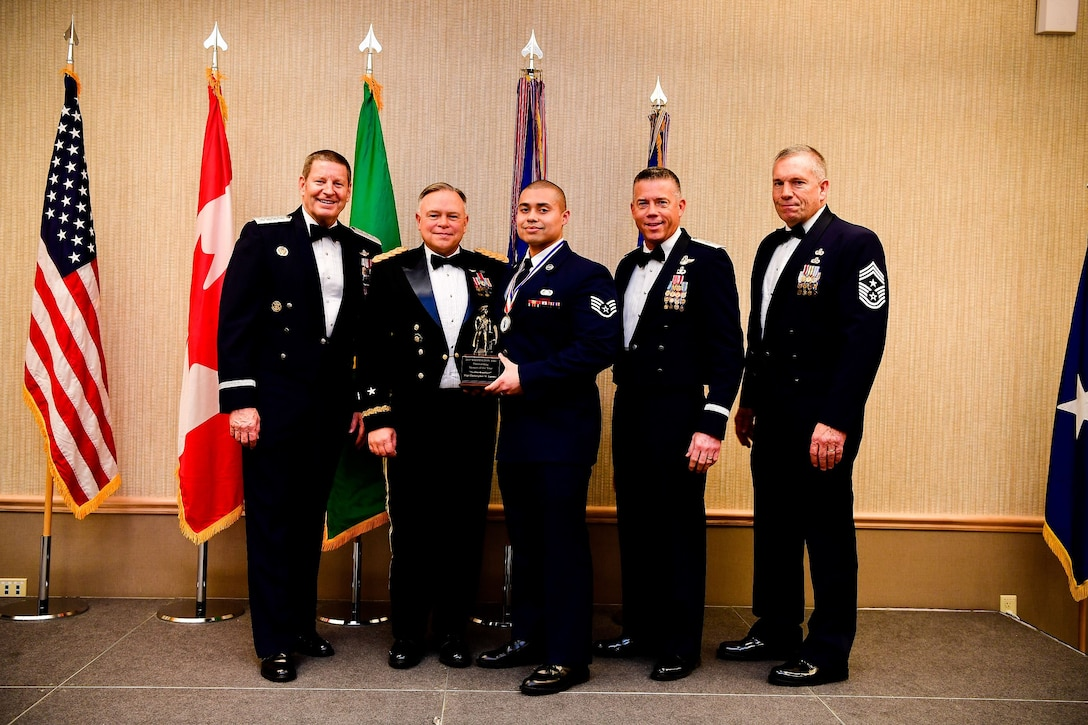 Staff Sgt. Christopher LaCour, a cyber systems operations journeyman with the 225th Support Squadron, Western Air Defense Sector, is presented with the Airman of the Year trophy at the Washington Air National Guard's 9th Annual Awards Banquet held at the American Lake Conference Center on Joint Base Lewis-McChord, Washington, Jan. 27, 2018.  LaCour was awarded the trophy for his outstanding contributions to the Washington Air National Guard over the last year.  Pictured from left to right are: Gen. Robin Rand, Air Force Global Strike Command and Air Forces Strategic-Air, U.S. Strategic Command commander; Maj. Gen. Bret Daugherty, Adjutant General of the Washington National Guard, LaCour, Brig. Gen. Jeremy Horn, commander of the Washington Air National Guard, and Chief Master Sgt. Max Tidwell, WA ANG command chief. (U.S. Air National Guard photo by Tech. Sgt. Timothy Chacon)