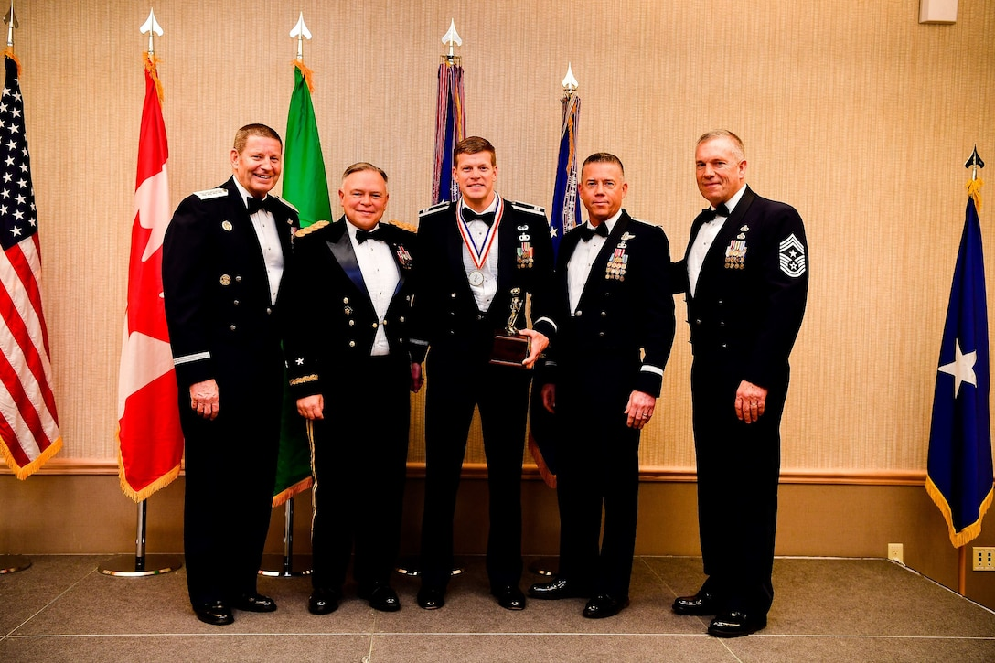 Capt. Nathan Carlson, an operations flight commander with the 116th Air Support Operations Squadron, 194th Wing, is presented with the Company Grade Officer of the Year trophy at the Washington Air National Guard's 9th Annual Awards Banquet held at the American Lake Conference Center on Joint Base Lewis-McChord, Washington, Jan. 27, 2018.  Carlson was awarded the trophy for his outstanding contributions to the Washington Air National Guard over the last year.  Pictured from left to right are: Gen. Robin Rand, Air Force Global Strike Command and Air Forces Strategic-Air, U.S. Strategic Command commander; Maj. Gen. Bret Daugherty, Adjutant General of the Washington National Guard, Carlson, Brig. Gen. Jeremy Horn, commander of the Washington Air National Guard, and Chief Master Sgt. Max Tidwell, WA ANG command chief. (U.S. Air National Guard photo by Tech. Sgt. Timothy Chacon)