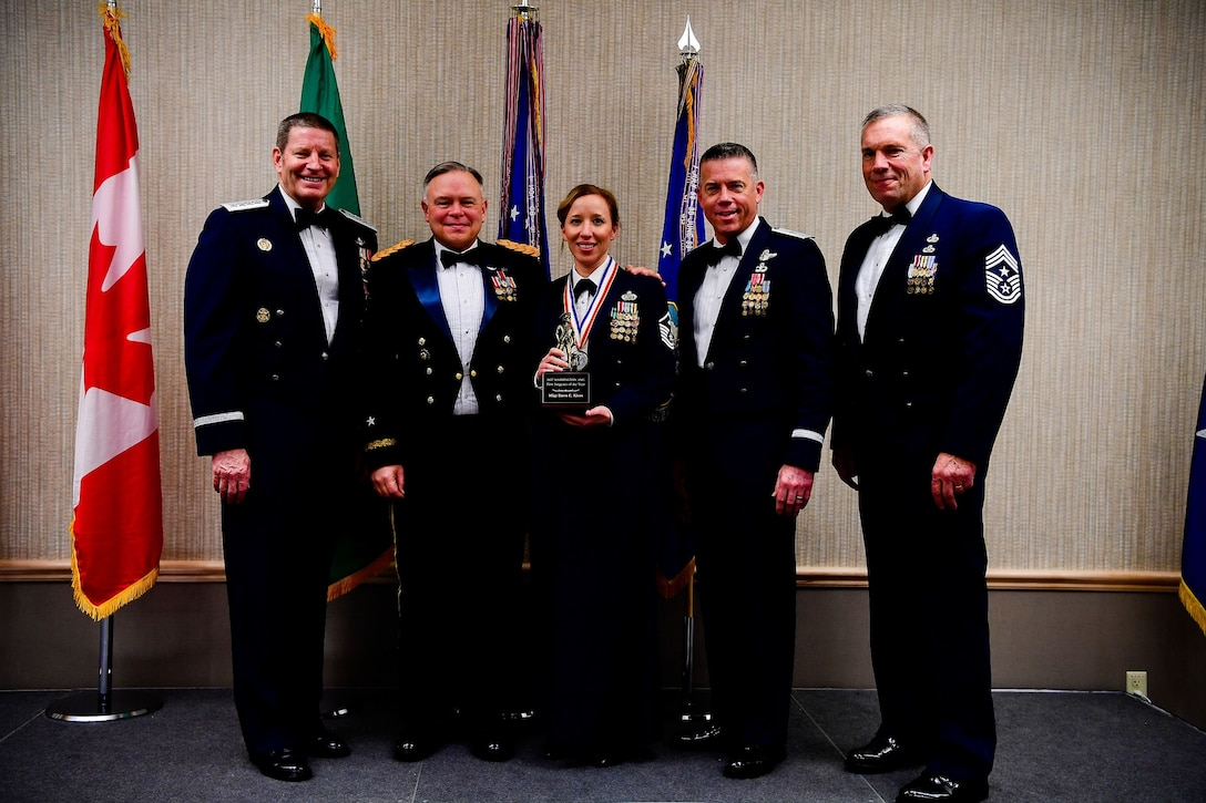 Master Sgt. Dawn Kloos, a first sergeant with the 225th Air Defense Group, Western Air Defense Sector, is presented with the First Sergeant of the Year trophy at the Washington Air National Guard's 9th Annual Awards Banquet held at the American Lake Conference Center on Joint Base Lewis-McChord, Washington, Jan. 27, 2018. Kloos was awarded the trophy for his outstanding contributions to the Washington Air National Guard over the last year.  Pictured from left to right are: Gen. Robin Rand, Air Force Global Strike Command and Air Forces Strategic-Air, U.S. Strategic Command commander; Maj. Gen. Bret Daugherty, Adjutant General of the Washington National Guard, Kloos, Brig. Gen. Jeremy Horn, commander of the Washington Air National Guard, and Chief Master Sgt. Max Tidwell, WA ANG command chief. (U.S. Air National Guard photo by Tech. Sgt. Timothy Chacon)