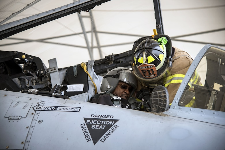 Airman 1st Class Orlando Chapman, 23d Civil Engineer Squadron (CES) firefighter, prepares to lift Charlie Johnson, 23d CES assistant fire chief of training, out of an A-10C Thunderbolt II, Jan. 24, 2018, at Moody Air Force Base, Ga. Firefighters from the 23d CES conducted A-10C Thunderbolt II extraction training to practice extinguishing an aircraft fire and quickly rescuing a pilot from an A-10. The 23d CES holds the extraction training twice annually and are evaluated on the amount of time it takes them to rescue a pilot from the cockpit. (U.S. Air Force photo by Airman Eugene Oliver)