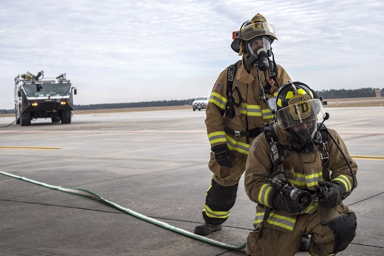 Firefighters from the 23d Civil Engineer Squadron (CES), prepare to shoot water out of a hose, Jan. 24, 2018, at Moody Air Force Base, Ga. Firefighters from the 23d CES conducted A-10C Thunderbolt II extraction training to practice extinguishing an aircraft fire and quickly rescuing a pilot from an A-10. The 23d CES holds the extraction training twice annually and are evaluated on the amount of time it takes them to rescue a pilot from the cockpit. (U.S. Air Force photo by Airman Eugene Oliver)