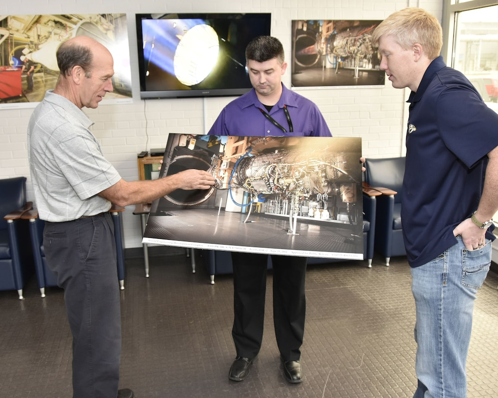 Using a photo of a Pratt & Whitney F135 engine in the AEDC Sea Level 2 test cell, Alan Hale, an AEDC analyst, left, describes how full frequency range screech analysis methodology is being used to reduce instability during aeropropulsion testing in AEDC engine test facilities at Arnold Air Force Base. Looking on is Jonathan Lister, center, and Wesley Cothran, right, AEDC team members who were also instrumental in developing and demonstrating the screech analysis methodology. (U.S. Air Force photo/Rick Goodfriend)