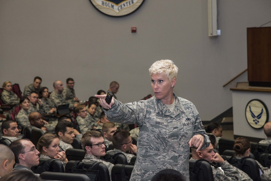 Master Sgt. Tiffany Dudley, Officer Training School military training instructor, teaches a class of approximately 100 OTS students, June 7, 2017, at Maxwell Air Force Base, Ala. During this classroom instruction, Dudley taught the students the proper wear of all combinations of the Air Force blues uniform. (U.S. Air Force photo by Senior Airman Alexa Culbert)