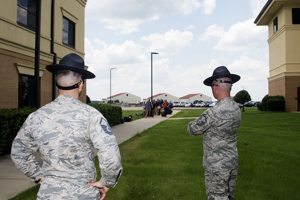 Officer Training School Military Training Instructors watch as the newest OTS students arrive on campus, June 28, 2017, at Maxwell Air Force Base, Ala. During the first day of training the students are sorted into their flights and taught basic military drill movement, from there they proceed to in-processing. (U.S. Air Force photo by Senior Airman Alexa Culbert)