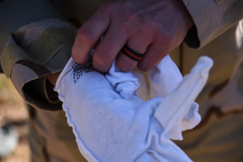 Airman puts on glove
