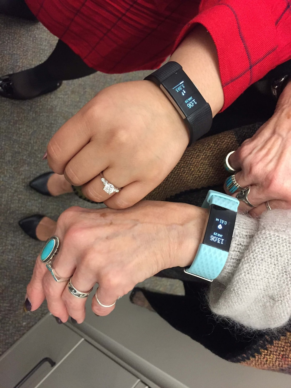 People wearing fitness trackers on their wrists.