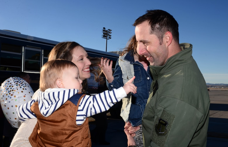 Capt. Lance, a weapons system officer assigned to the 37th Bomb Squadron, sees his family for the first time in over six months during a redeployment at Ellsworth Air Force Base, S.D., Jan. 24, 2018. B-1 bomber aircrews conducted sorties close to South Korea's norther border as part of the U.S. Pacific Command's Continuous Bomber Presence mission. (U.S. Air Force photo by Airman 1st Class Donald Knechtel)