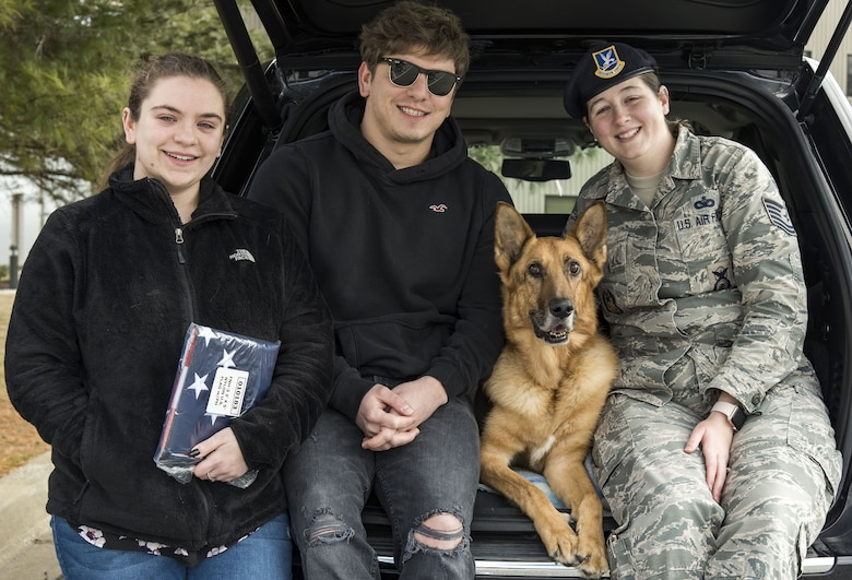 Mya Spangenberg along with her father, retired Tech. Sgt. Jason Spangenberg; Tech. Sgt. Rachel Weis, 436th Airlift Wing inspector general inspections NCO in charge; and retired Military Working Dog Rico pose for a photo Jan. 24, 2018, at the Veterinary Treatment Facility on Dover Air Force Base, Del. MWD Rico was humanely euthanized shortly after being carried into the facility by Spangenberg, his owner. (U.S. Air Force photo by Roland Balik)