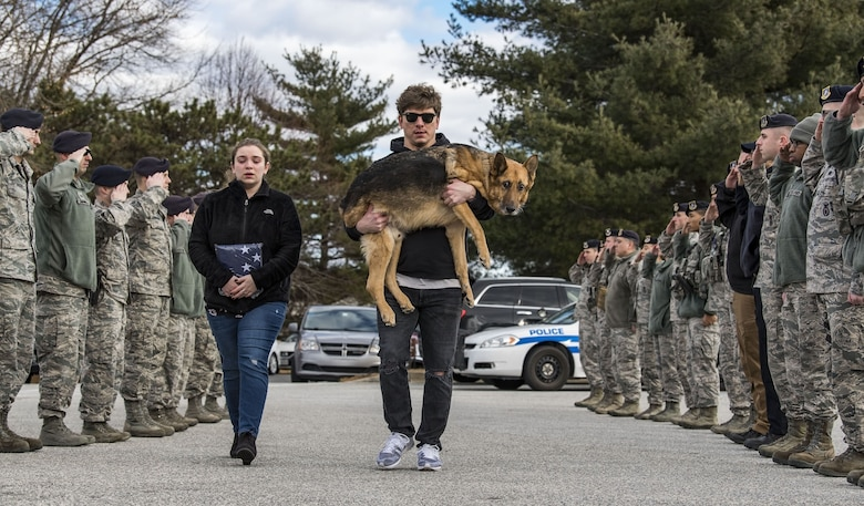 Members of the 436th Security Forces Squadron render a final salute to retired Military Working Dog Rico as his former handler and current owner, retired Tech. Sgt. Jason Spangenberg, carries him to the Veterinary Treatment Facility Jan. 24, 2018, on Dover Air Force Base, Del. Mya Spangenberg accompanied her father as they walked through the cordon. (U.S. Air Force photo by Roland Balik)