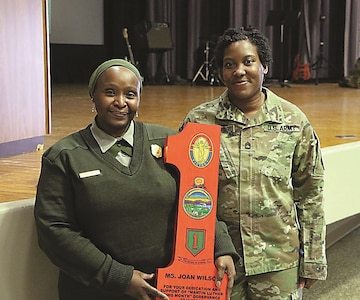 "Sgt. 1st Class Daralyn Williams-Saulsberry, right, 1st Infantry Division Sustainment Brigade equal opportunity advisor, poses for a photo with guest speaker Joan Wilson, a park ranger at the Brown v. Board of Education National Historic Site in Topeka, Kansas, after the Martin Luther King Jr. observance Jan. 17 at Fort Riley. Wilson was presented a wooden ""Big Red One"" as a token of appreciation for being the guest speaker at the observance."