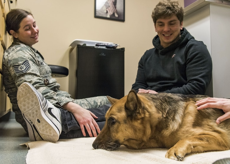 Tech. Sgt. Rachel Weis, 436th Airlift Wing inspector general inspections NCO in charge, and retired Tech. Sgt. Jason Spangenberg spend a few moments in an examination room with their retired Military Working Dog Rico Jan. 24, 2018, at the Veterinary Treatment Facility on Dover Air Force Base, Del. MWD Rico was humanely euthanized by a U.S. Army veterinarian due to his declining health condition caused by Canine Degenerative Myelopathy. (U.S. Air Force photo by Roland Balik)
