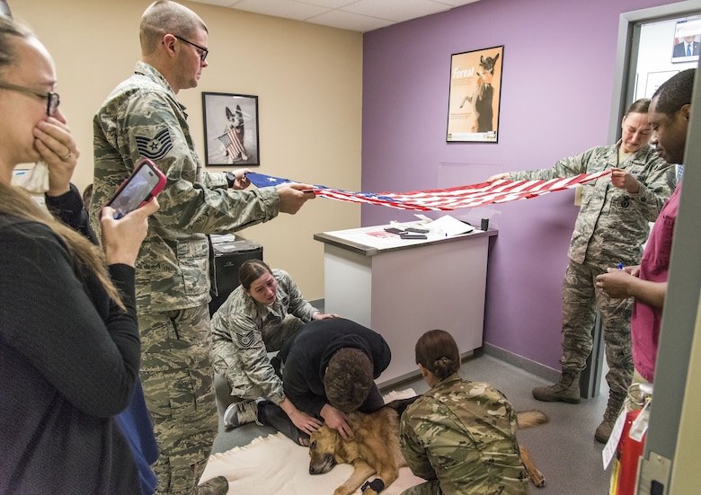 Tech. Sgt. Matthew Salter, 436th Security Forces Squadron military working dog kennel master, and Staff Sgt. Ashley Beattie, 436th SFS unit deployment manager, hold the U.S. flag over retired Military Working Dog Rico Jan. 24, 2018, at the Veterinary Treatment Facility on Dover Air Force Base, Del. MWD Rico was humanely euthanized by a U.S. Army veterinarian due to his declining health caused by Canine Degenerative Myelopathy. (U.S. Air Force photo by Roland Balik)
