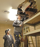 Mark Sekulich, left, helps Bryan Finnegan, plumbers with Operations and Maintenance Division - Directorate of Public Works, check damages left behind by a burst pipe in one of the buildings on Custer Hill Jan. 19. Public Works estimated the total of damages this winter season so far to have reached $1 million.