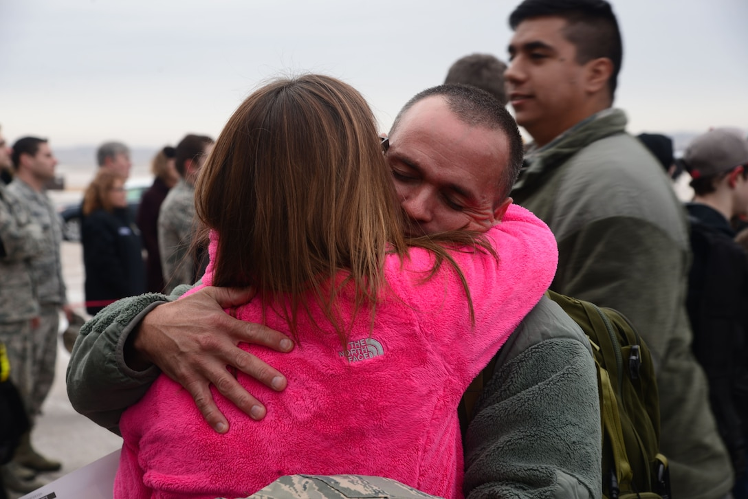 Senior Master Sgt. Derek Hulsey, the 28th Aircraft Maintenance Squadron first sergeant, hugs his wife, Master Sgt. Deborah Hulsey, the 28th Medical Operations Squadron superintendent, at Ellsworth Air Force Base, S.D., Jan. 29, 2018. B-1 Bombers from the 37th Bomb Squadron and Airmen from the 37th Aircraft Maintenance Unit returned from a six-month deployment to Andersen AFB, Guam, where they took part in the Continuous Bomber Presence mission. (U.S. Air Force photo by Airman 1st Class Donald Knechtel)