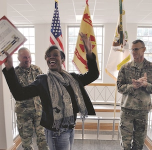 Fort Riley Garrison Commander Col. John D Lawrence, left, and Garrison Command Sgt. Maj. James L. Collins, right, clap for Benita Edwards, Employment Readiness Program manager with Army Community Service, during the Garrison Awards Ceremony Jan. 19 at Summerall Hall. She received awards recognizing her as Employee of the Month and Garrison Employee of the Quarter for the first quarter of fiscal year 2018.