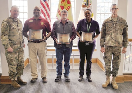 Fort Riley Garrison Commander Col. John Lawrence, left, and Garrison Command Sgt. Maj. James L. Collins, right, present risk management awards to three individuals for their hard work in maintaining safety in the Garrison Safety Office and across the garrison. The three award recipients are Ronald Clasberry, left, deputy garrison safety manager; Thomas Anderson, middle, safety specialist; Dawn Douglas, right, safety and occupational health specialist with the garrison safety office.