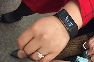 A woman shows a fitness tracker on her wrist.